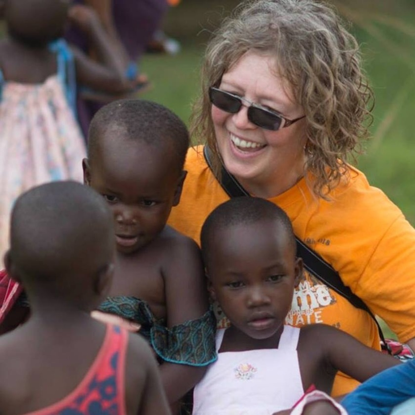 Cheryl in Uganda with beautiful orphans. Photo by Mike Kelly, PhotoEmagery