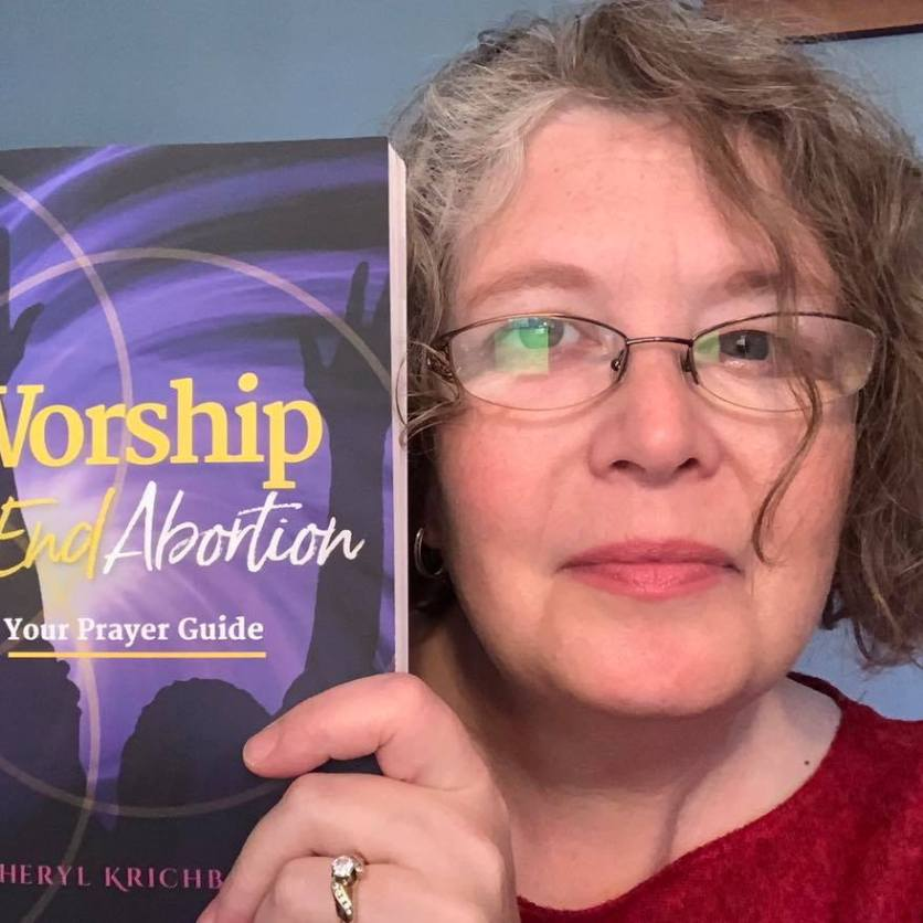 Cheryl holding her Worship to End Abortion book