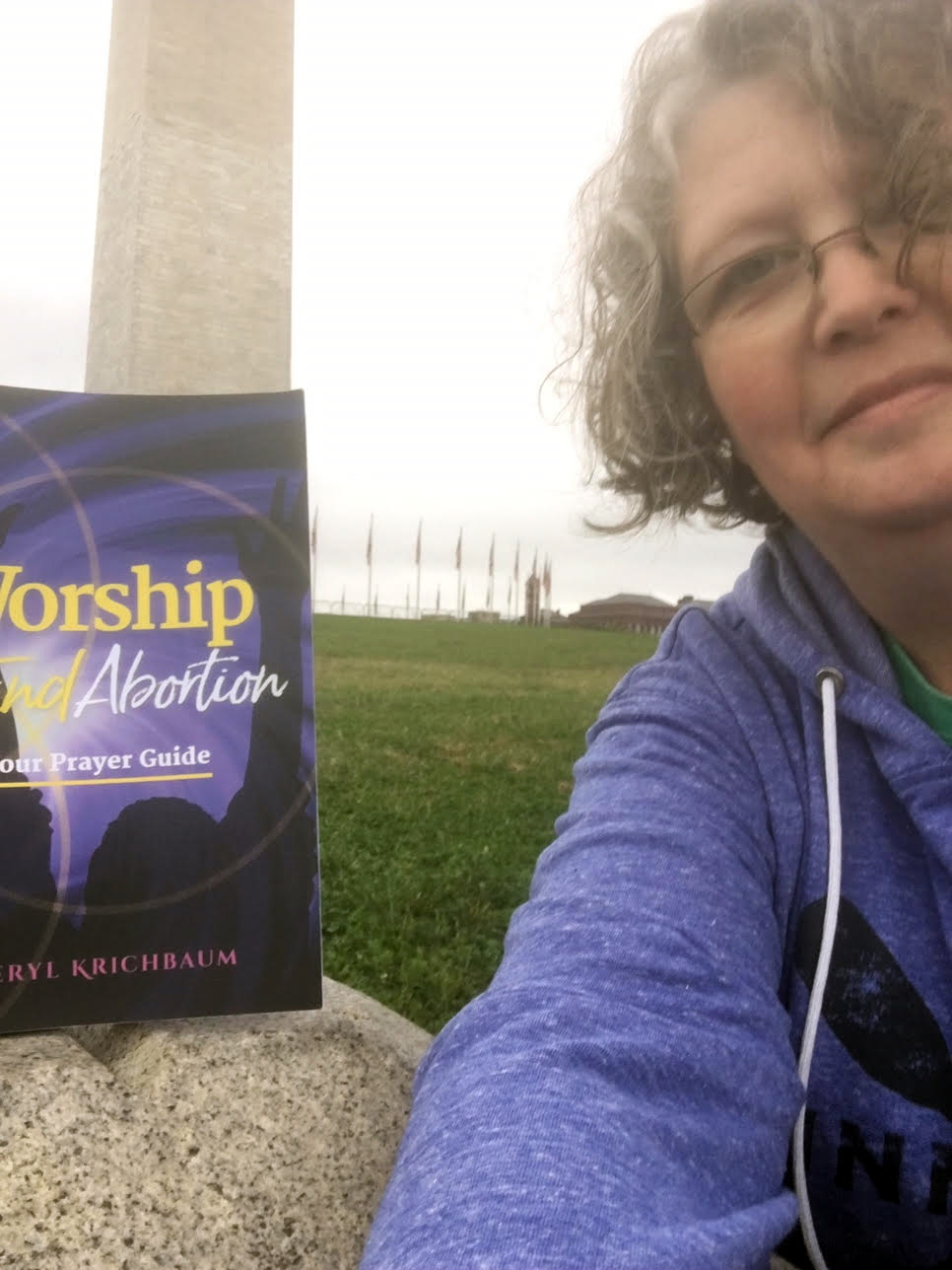 Cheryl at Jefferson Pier with her prayer guide;; the Washington Monument in the background